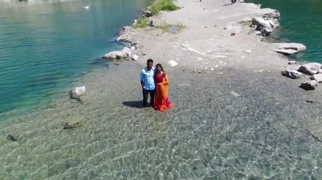a couple standing on the lake side
